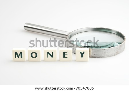 Money word and magnifying glass - stock photo