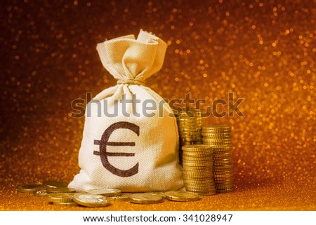 Moneybag and Euro coins over defocused lights - stock photo