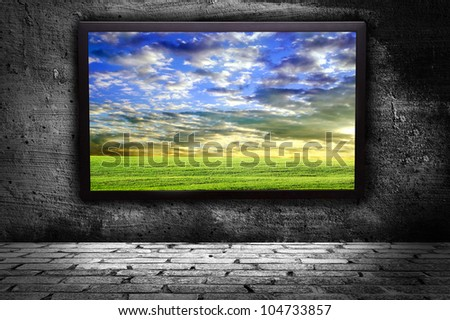 monitor with thea picture of of pure field against the gray walls - stock photo