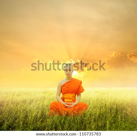 Monk meditating in grass fields and sunset - stock photo