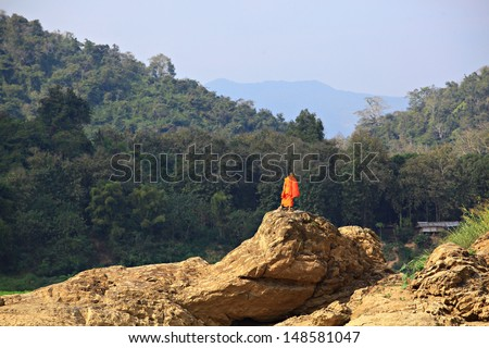 Monk Stand on Rock be side Mekong River Luang prabang ,Laos.  - stock photo