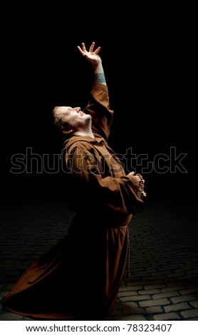 Monk standing on kneels and asking God for help - stock photo
