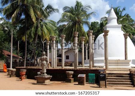 Monk, statue and Ambasthala dagaba in Mihintale, Sri Lanka - stock photo