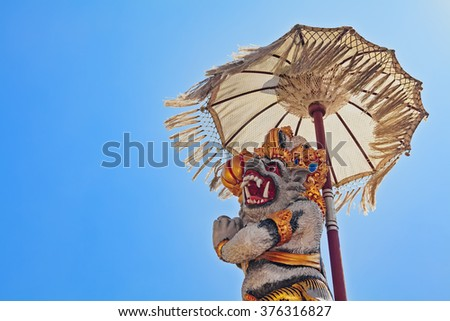 Monkey Hanuman - traditional protective spirit and Bali island symbol under ceremonial umbrella in front of temple. Arts, religion and culture festivals of Indonesian people. Asian travel backgrounds. - stock photo