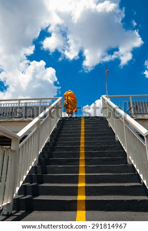 Monks is steps up the stairs of the pedestrian overpass in the city. - stock photo