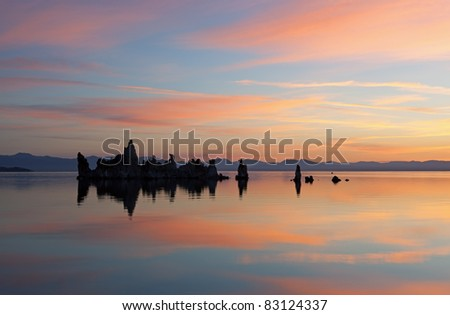 Mono Lake at dawn with tufa formations and reflections in calm water, California, USA - stock photo