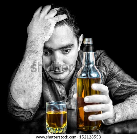 Monochromatic image of a drunk desperate hispanic  man with an whisky bottle isolated on black (the bottle and glass have color) - stock photo