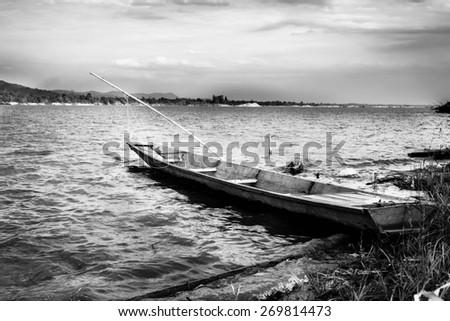 Monochrome Abandoned boat on the lake - stock photo