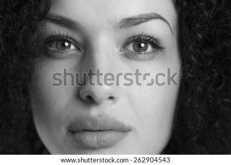 Monochrome black and white close up of a beautiful seriously looking woman. - stock photo