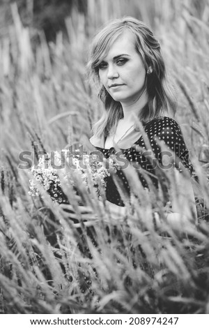 Monochrome closeup portrait of woman holding bunch of flowers at field - stock photo