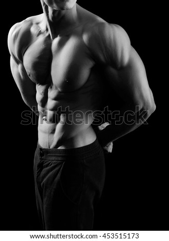 Monochrome cropped shot of a sexy ripped muscular man posing in studio showing off his abs - stock photo