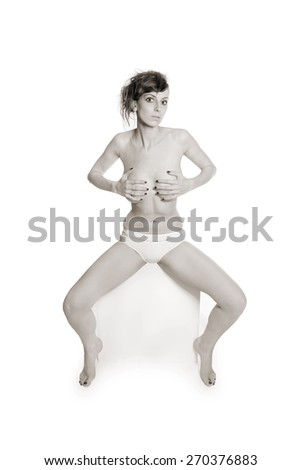 Monochrome fashion portrait of a beautiful topless woman in white panties, in front of white studio  background, her private parts are not visible - stock photo