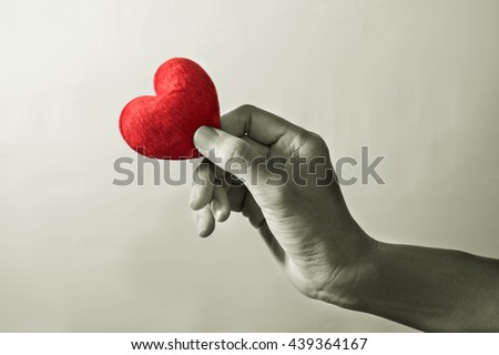 Monochrome filtered, woman hand with red heart. - stock photo