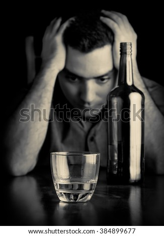 Monochrome image of a desperate man drinking alone - stock photo