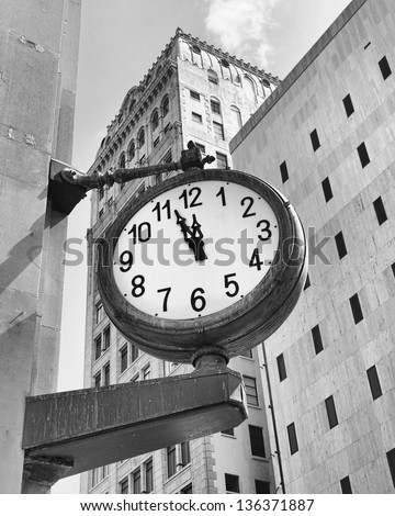 monochrome image of a downtown Miami street clock at a few minutes before twelve - stock photo