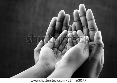 Monochrome image of  hands of a kid covered by hands of as elder. Ideal for concepts of care and protection - stock photo