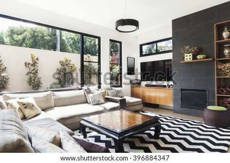 Monochrome living room with wood and grey tiling accents and chevron pattern rug - stock photo