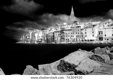 monochrome of a town on the adriatic coast dominated by a venetian bell tower and statue of an angel - stock photo