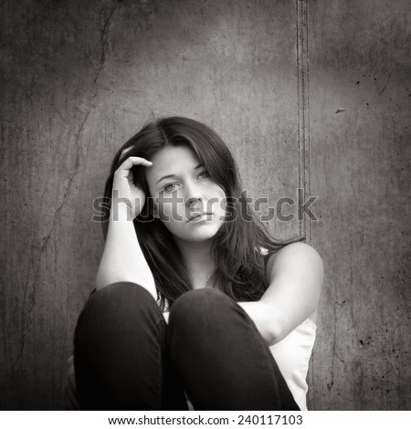 Monochrome outdoor portrait of a sad teenage girl looking thoughtful about troubles in front of a gray wall - stock photo