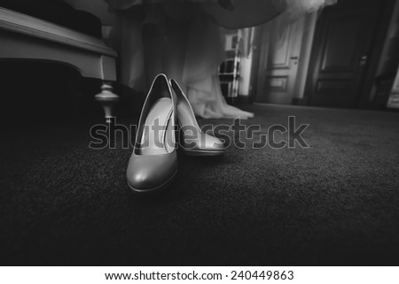 monochrome photo of shoes on carpet in room - stock photo