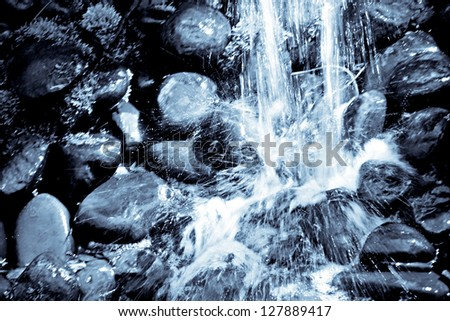 Monochrome photo of stone waterfall in botanical garden - stock photo