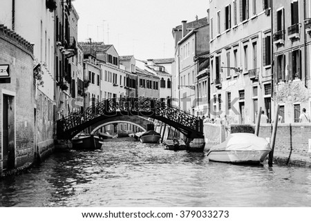 Monochrome photo of the venetian canal with gondola across the canal. Historic houses of the Grand Canal in Venice, Italy. Narrow Canal in Venice, Italy. Black and white photo. - stock photo