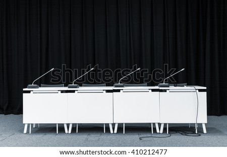 Monochrome picture of conference stand table with microphones in a meeting room - stock photo