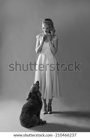 Monochrome portrait in black and white of beautiful blonde lady in vintage dress and high heeled shoes feeding her Spaniel dog treats  - stock photo