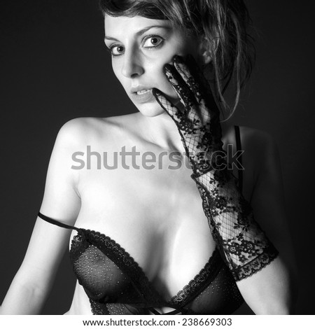 Monochrome portrait of a beautiful woman in sexy lingerie in front of black background - stock photo