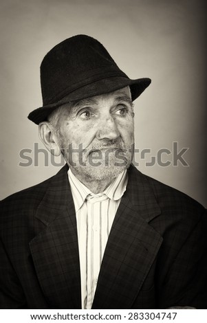 Monochrome portrait of an old man with hat  - stock photo
