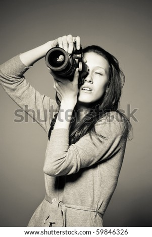 Monochrome portrait of beautiful female photographer shooting - stock photo