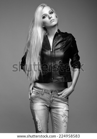 Monochrome portrait of blonde young woman in ragged jeans and black jacket on gray background - stock photo