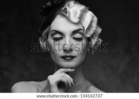 Monochrome portrait of elegant blond retro woman   with beautiful hairdo and little hat - stock photo