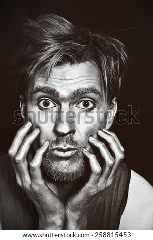 Monochrome portrait of young attractive man with a silvery makeup on her face and hands against a black background - stock photo