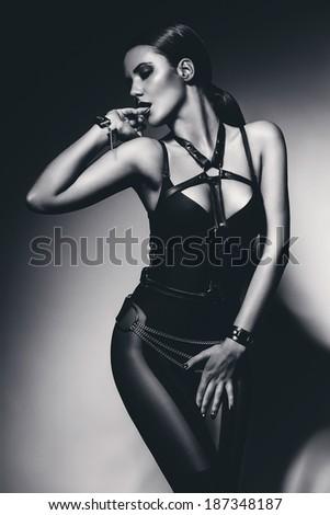 monochrome sexy bdsm woman biting finger - stock photo