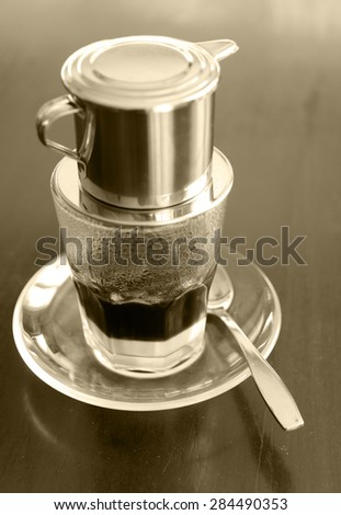 monotone picture of traditional Vietnamese coffee, slow brewing with the condensed milk at the bottom - stock photo