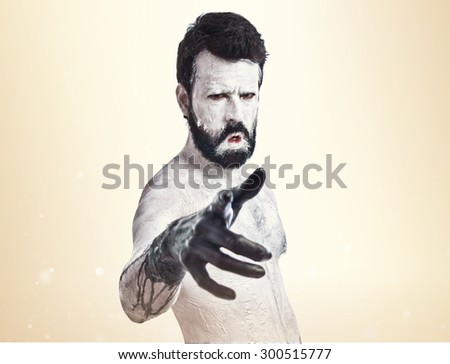 Monster pointing to the front over ocher background - stock photo