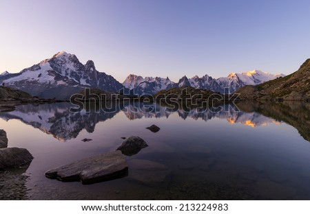 Mont Blanc Massif Reflected in Lac Blanc at Sunrise, Graian Alps, France - stock photo