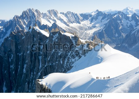 Mont Blanc mountaneers walking on snowy ridge. The mountain is the highest in the alps and the European Union. - stock photo
