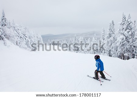 MONT-TREMBLANT, QC, CANADA -FEBRUARY 9: A boy is skiing down an easy slope at Mont-Tremblant Ski Resort on February 9, 2014. It is the best ski resort in Eastern North America. - stock photo