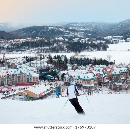 MONT-TREMBLANT, QC, CANADA -FEBRUARY 9: Skiers and snowboarders are sliding down the main slope at Mont-Tremblant Ski Resort on February 9, 2014. It is the best ski resort in Eastern North America. - stock photo