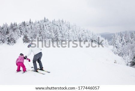 MONT-TREMBLANT, QUEBEC, CANADA - FEBRUARY 9:  A mother is teaching her young daughter to ski down an easy slope at Mont-Tremblant on February 9, 2014, the best ski resort in Eastern North America.  - stock photo