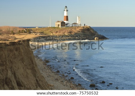 Montauk Lighthouse with an eroding bluff in the foreground on the Eastern tip of Long Island, NY - stock photo
