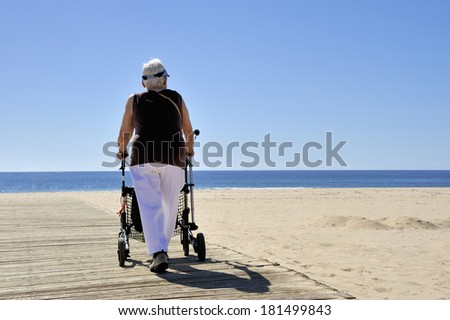 MONTEGORDO, PORTUGAL- FEBRUARY 22, 2014; Old lady with rollator at the beach on a sunny day.February 22, 2014 Montegordo, Portugal - stock photo