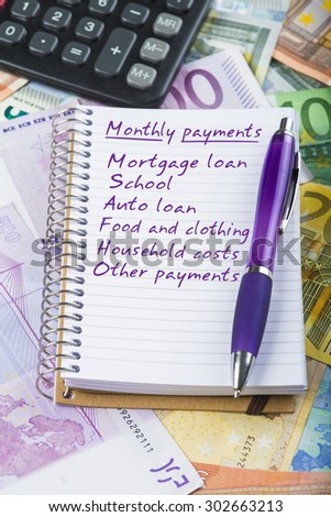 Monthly payments list on a notebook over  a money background made of banknotes - stock photo