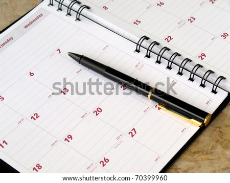 monthly planner with pen on the table - stock photo