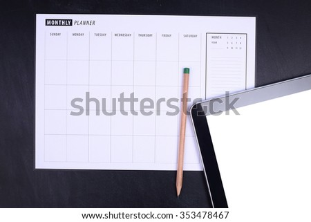 Monthly planner with pencil and tablet - stock photo