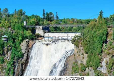 Montmorency Falls with rainbow and blue sky near Quebec City. - stock photo