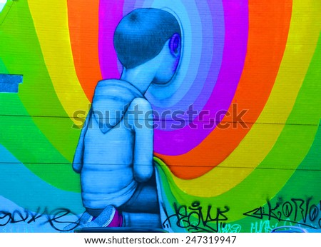 MONTREAL CANADA JAN 25: Street art boy looking in hole on jan 25 2015 in Montreal Canada. Montreal. is the perfect place to walk in the back alleys and abandoned areas, looking for street art.  - stock photo