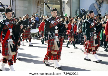 MONTREAL, CANADA - MARCH 20: Irishmen in their kilt playing their bagpipes during the St. Patrick's Day Parade on March 20, 2011 in Montreal, Canada. It's a traditional Irish holiday parade. - stock photo